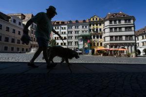 Ein Mann mit Hund laeuft auf dem Untermarkt in Goerlitz (Sachsen)bei den Temperaturen um die 30 Grad. //Foto: Pawel Sosnowski